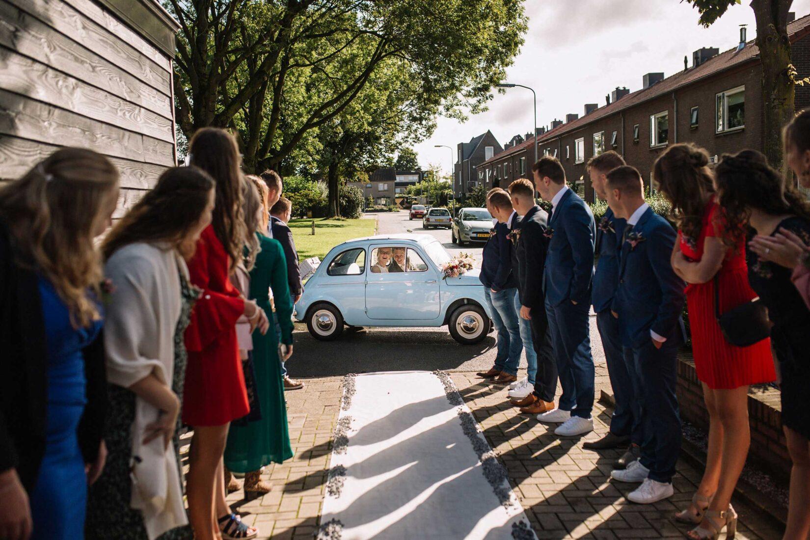 Bruidspaar in auto wordt verwelkomd door gasten